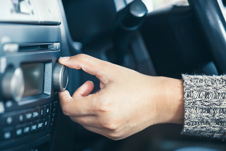 Photo for Woman hand adjusting the sound volume of car radio while driving a car in vintage color tone - Royalty Free Image