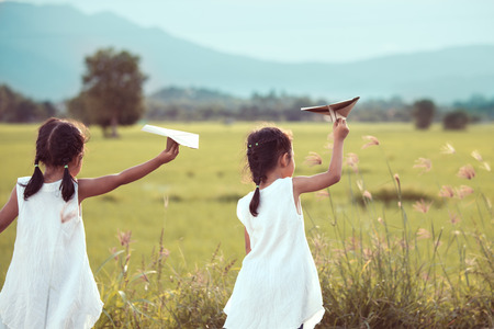 Foto de Back view of two asian child girls playing toy paper airplane together in the field in vintage color tone - Imagen libre de derechos
