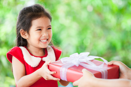 Photo pour Parent giving Christmas gift to cute asian child girl on green nature background. Christmas concept. - image libre de droit