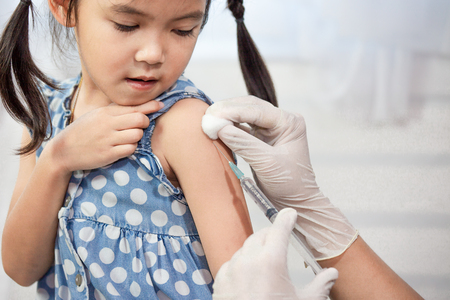 Foto de Doctor injecting vaccination in arm of asian little child girl,healthy and medical concept - Imagen libre de derechos