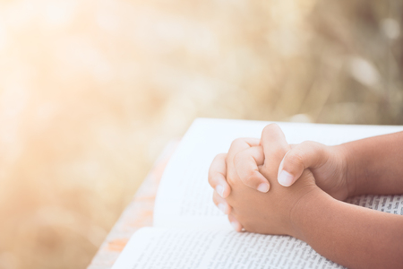 Foto de Little child girl hands folded in prayer on a Holy Bible for faith,spirituality and religion concept in vintage color tone - Imagen libre de derechos