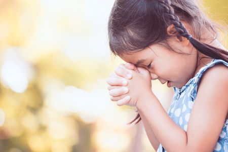 Foto de Cute asian little child girl praying with folded her hand for faith,spirituality and religion concept - Imagen libre de derechos