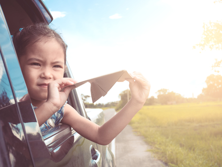 Photo pour Cute asian little child girl having fun to play with toy paper airplane out of car window in the countryside in vintage color tone - image libre de droit