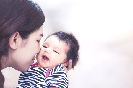 Photo for Young asian mother hugging and kissing her newborn baby girl with love in vintage color tone - Royalty Free Image