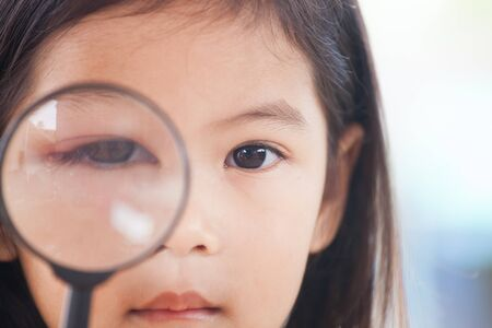 Photo for Closeup of asian child girl eye swell from bacteria virus looking through a magnifying glass - Royalty Free Image