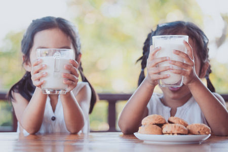 Foto de Two cute asian little child girls holding  glass of milk for breakfast together with happiness - Imagen libre de derechos