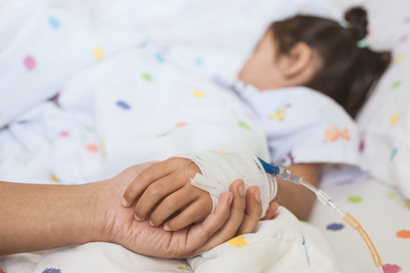 Photo pour Mother hand holding sick daughter hand who have IV solution bandaged with love and care while she is sleeping on bed in the hospital - image libre de droit