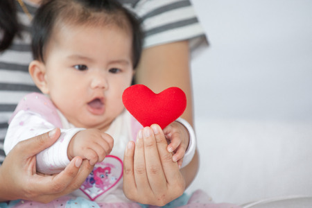 Foto de Cute asian baby girl  playing with her mother and try to catch red heart on mother hand with fun and curious - Imagen libre de derechos