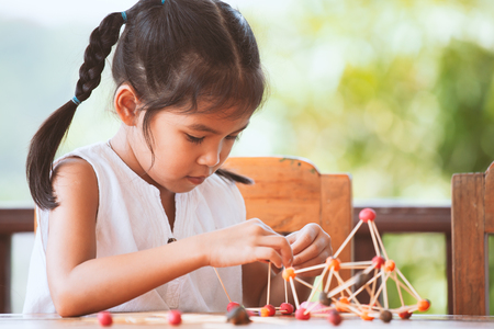 Foto de Cute asian child girl playing and creating with play dough and toothpick. Child concentrated with play dough building a molecule model. - Imagen libre de derechos