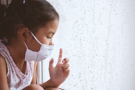 Foto de Sick asian little child girl wear protective mask looking outside through the window in the rainy day - Imagen libre de derechos