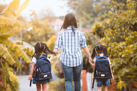 Photo for Back to school. Asian mother and daughter pupil girl with backpack holding hand and going to school together in vintage color tone - Royalty Free Image