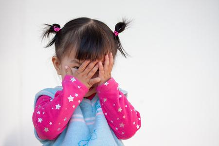 Foto de Cute asian baby girl closing her face and playing peekaboo or hide and seek with fun - Imagen libre de derechos