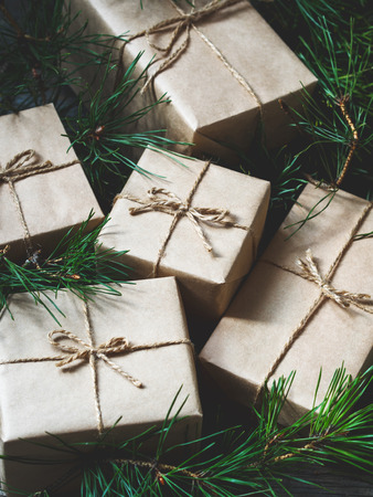 Close-up of Christmas gifts Packed in kraft paper among the branches of the Christmas tree. New year greeting card concept, holiday mood. Christmas or New Year background.