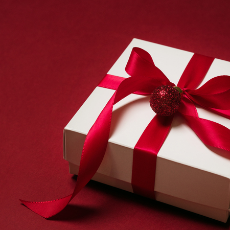 Photo for Top view of gift box with red ribbon over red background - Royalty Free Image