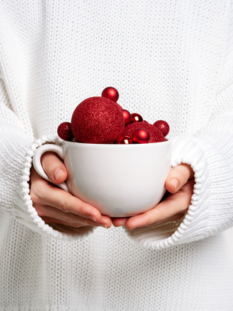 Photo for Woman in warm white sweater holding white mug in hands with christmas balls like ice cream. Concept for New year mockup. - Royalty Free Image