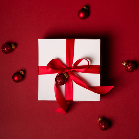 Photo for Top view gift white box with red ribbon decorated with a small Christmas toy on a red background - Royalty Free Image