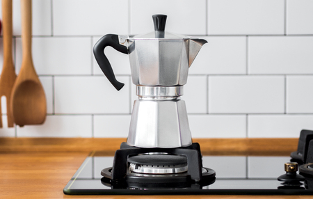 Foto per Closeup of Moka coffee pot on a gas stove against a wall with white tiles in kitchen with free space for text. scandinavian design interior. - Immagine Royalty Free