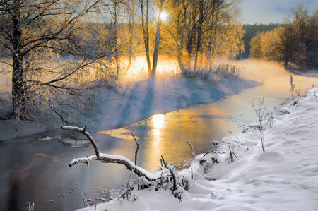 Scandinavian small river in winter, with sunbeams filtering through bare birch trees