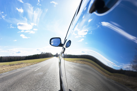 Photo pour Blue sky with clouds and asphalt road reflected in side of car - image libre de droit