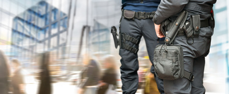 Photo pour Armed policemen on guard in busy street with modern glass buildings and people walking - image libre de droit