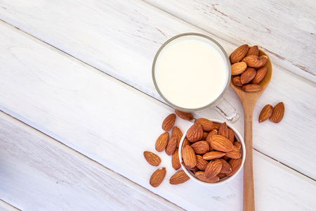 Photo pour Close up top view of healthy almond milk in drinking glass with seed in white cup and wooden spoon on white wooden table plate with copy space - image libre de droit