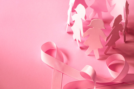 Foto de Sweet pink ribbon shape with girl paper doll on pink background  for Breast Cancer Awareness symbol to promote  in october month campaign - Imagen libre de derechos