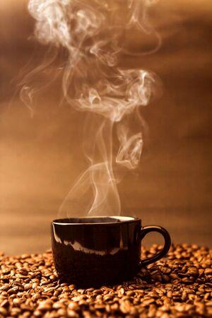 Foto de still life of the warm black cup of coffee on  roasted coffee beans - Imagen libre de derechos