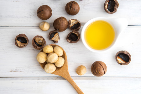 Photo for The Macadamia Nut Oil and peeled macadamia nut   on white table , ?use for Healthy Skin and Hair and Natural Healing Oil Treatment , overhead and top view - Royalty Free Image
