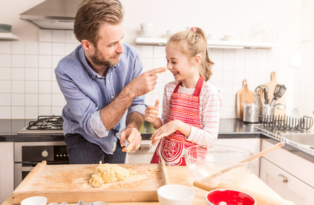 Foto de Smiling caucasian father and daughter having fun while preparing cookie dough in the kitchen. Baking - happy family time. - Imagen libre de derechos