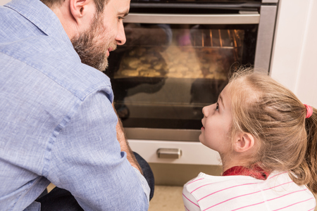 Photo pour Happy caucasian father and daughter waiting near the kitchen oven for the homemade cookies. Baking - happy family time. - image libre de droit