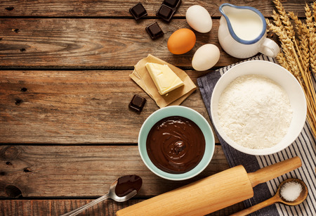 Foto de Baking chocolate cake in rural or rustic kitchen. Background layout with free text space. - Imagen libre de derechos