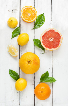 Photo for Citrus fruits (lemon, grapefruit and orange) with fresh wet leaves on white vintage wooden table - still life from above - Royalty Free Image