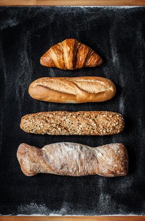 Foto de Different kinds of bread rolls on black chalkboard from above. Kitchen or bakery poster design. - Imagen libre de derechos