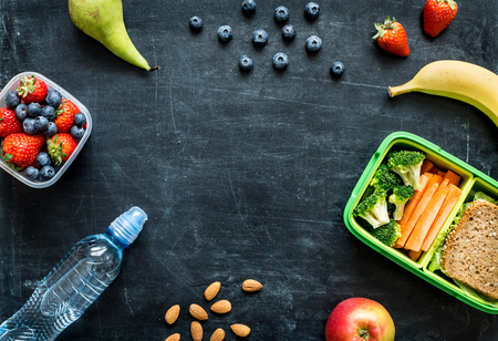 Photo pour School lunch box with sandwich, vegetables, water, almonds and fruits on black chalkboard. Healthy eating habits concept - background layout with free text space. Flat lay composition (top view). - image libre de droit