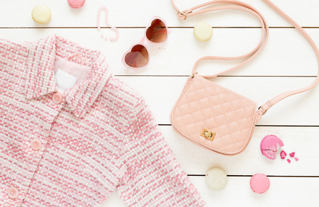 Foto de Pastel theme mood board with pink jacket and fashion accessories (bag, sunglasses) for girls. White rustic wooden background. Flat lay composition (from above, top view). - Imagen libre de derechos