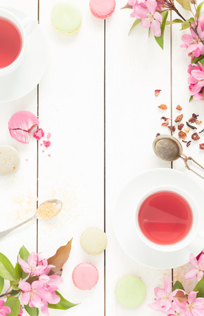 Photo for Pink fruity tea and pastel french macarons cakes on rustic white wooden background. Dessert in a garden. Flat lay composition (from above, top view). Free text space. - Royalty Free Image