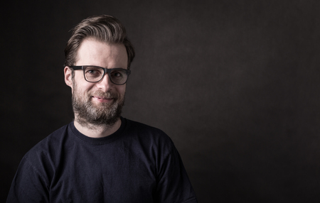 Photo for Portrait of happy smiling forty years old caucasian man in casual t-shirt and glasses. Black background, dark moody concept. Layout with free text (copy) space.  - Royalty Free Image