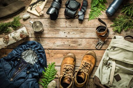 Foto de Camping or adventure trip scenery concept. Backpack, jacket, boots, belt,   camera on wooden background captured from above (flat lay). Layout with free text (copy) space. - Imagen libre de derechos