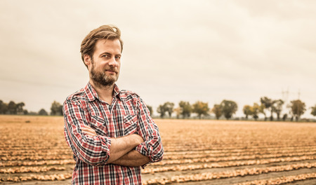 Foto de Forty years old caucasian farmer in plaid shirt standing proud in front of onion field. Agriculture - country outdoor scenery (landscape). - Imagen libre de derechos