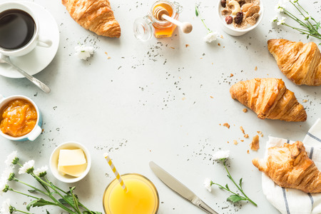 Foto de Continental breakfast captured from above (top view, flat lay). Coffee, orange juice, croissants, jam, honey and flowers. Grey stone worktop as background. Layout with free text (copy) space. - Imagen libre de derechos