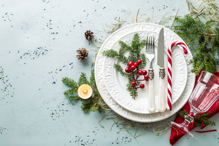 Foto de Elegant christmas table setting design captured from above (top view, flat lay). White plates, glass, cutlery (silverware), candy cane and decorations. Background layout with free text (copy) space. - Imagen libre de derechos