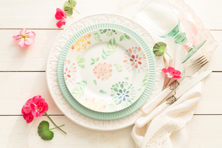 Foto de Easter, spring or summer table setting design captured from above (top view, flat lay). Ornamental plates, glass, cutlery and flowers. White wooden background. Outdoor garden party or picnic concept. - Imagen libre de derechos