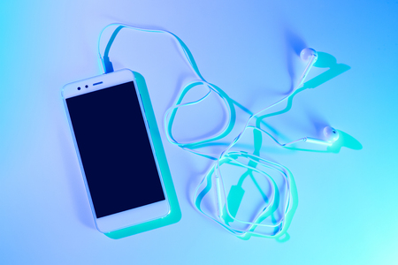 Photo for Mobile phone (smartphone) and earphones. Colorful (multicolor tonal transitions) background. - Royalty Free Image