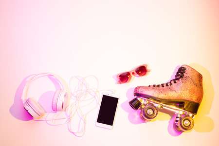 Foto de Retro pink glittery roller skates, mobile phone (smartphone), headphones and sunglasses captured from above (top view, flat lay). Fun, recreation and active lifestyle - background (free text space). - Imagen libre de derechos