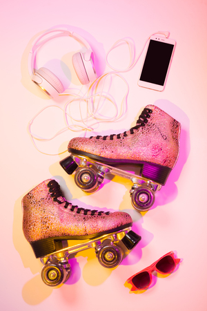Foto de Retro pink glittery roller skates, mobile phone (smartphone), headphones and sunglasses captured from above (top view, flat lay). Fun, recreation and active life style poster concept - summer vibes. - Imagen libre de derechos