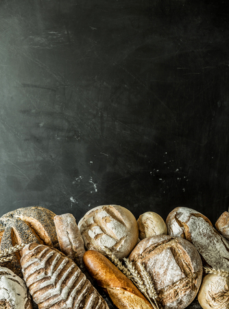 Photo for Bakery stall - gold rustic crusty loaves of bread and buns exposed on black chalkboard background. Poster layout with free copy (text) space. - Royalty Free Image
