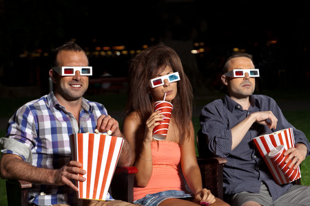 Photo for three friends watching a movie at cinema outdoors - Royalty Free Image