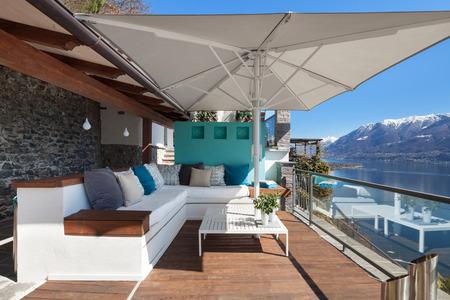 Foto de Terrace lounge with comfortable divans and lake view in a luxury house - Imagen libre de derechos