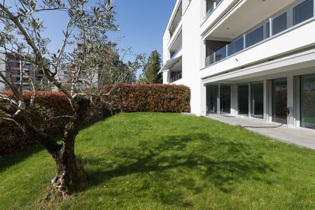 Foto de Modern house exterior with well-kept green lawn. Sunny day - Imagen libre de derechos