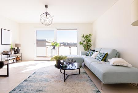 Foto de Modern living room with designer sofa and coffee table. Window with view. Nobody inside - Imagen libre de derechos